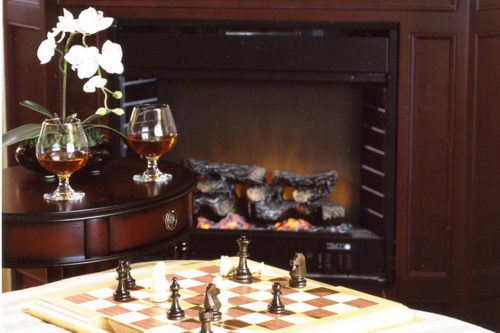 Table with chessboard and two glasses of brandy