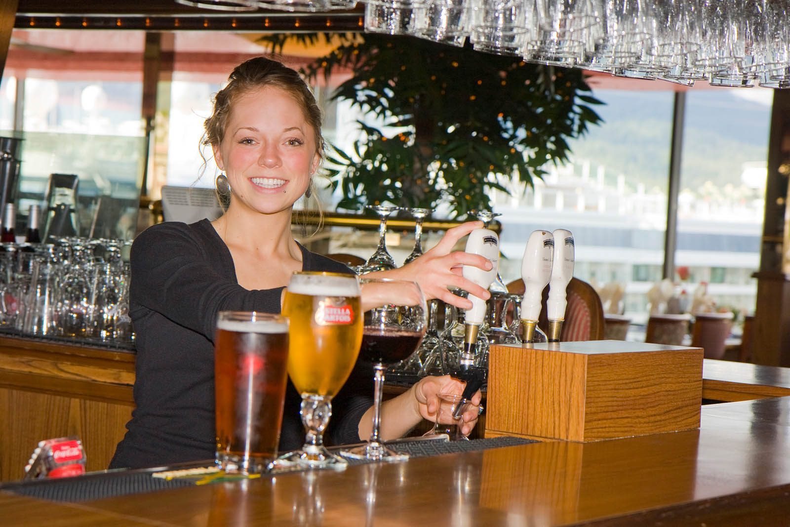 Bartender filling a glass from taps