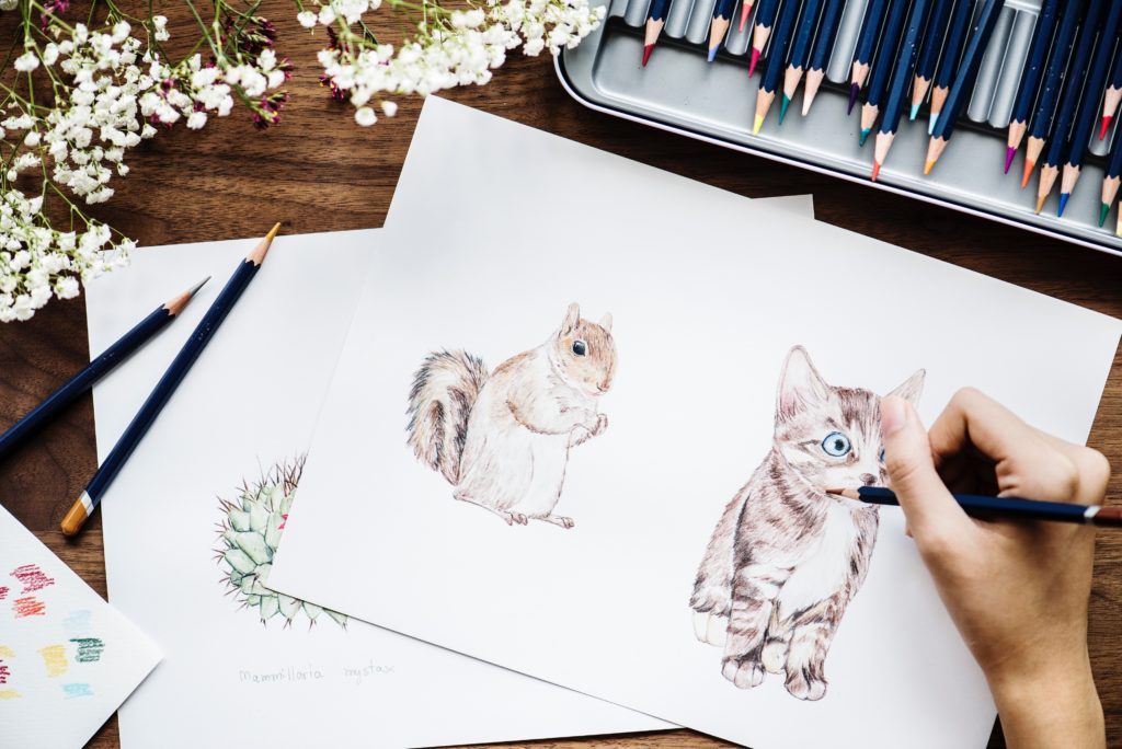 Hand creating realistic drawing of squirrel and kitten
